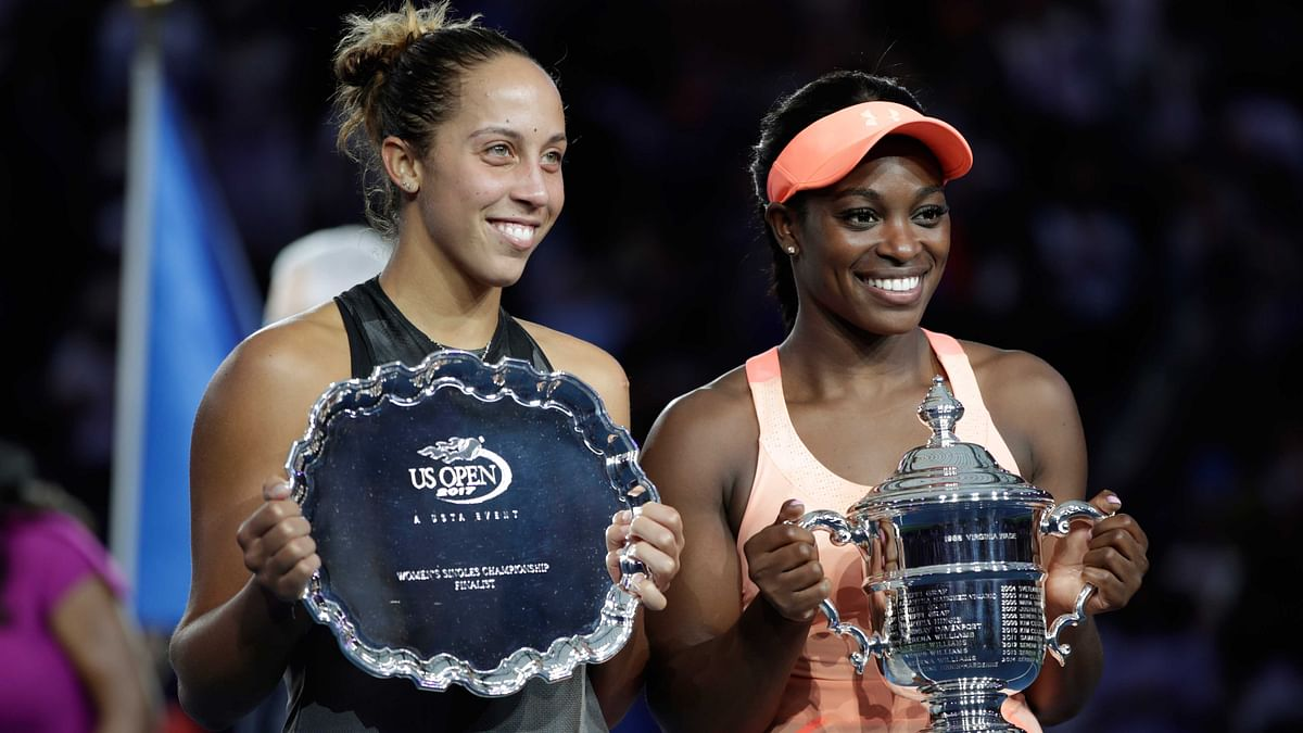 Madison Keys, of the United States, left, holds up the finalist trophy as Sloane Stephens, of the United States, holds the championship trophy after Stephens won the women's singles final of the US Open
