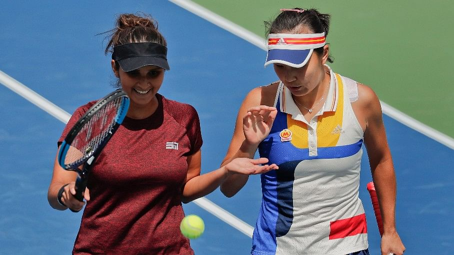 Sania Mirza slaps hands with doubles partner Peng Shuai during the doubles semifinals of the US Open.