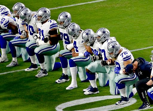 The Dallas Cowboys take a knee prior to the national anthem prior to an NFL football game against the Arizona Cardinals on Monday, 25 September 2017, in  Arizona.