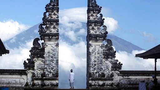 Balinese man watches Mount Agung volcano almost covered with clouds as he stands at a temple in Karangasem, Bali, Indonesia