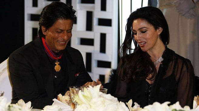 SRK and Monica Belluucci share a table at an event.