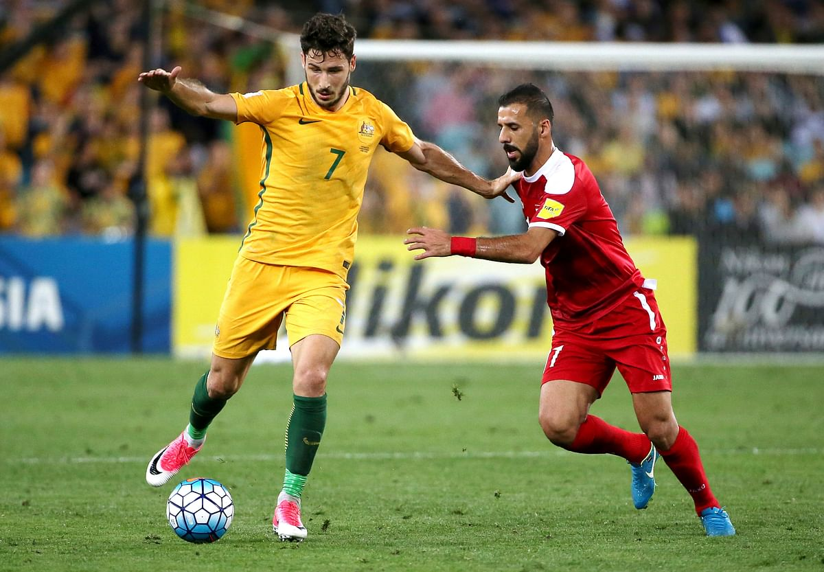 Australia's Mathew Leckie, left, and Syria's Ouday Abduljaffal compete for the ball.