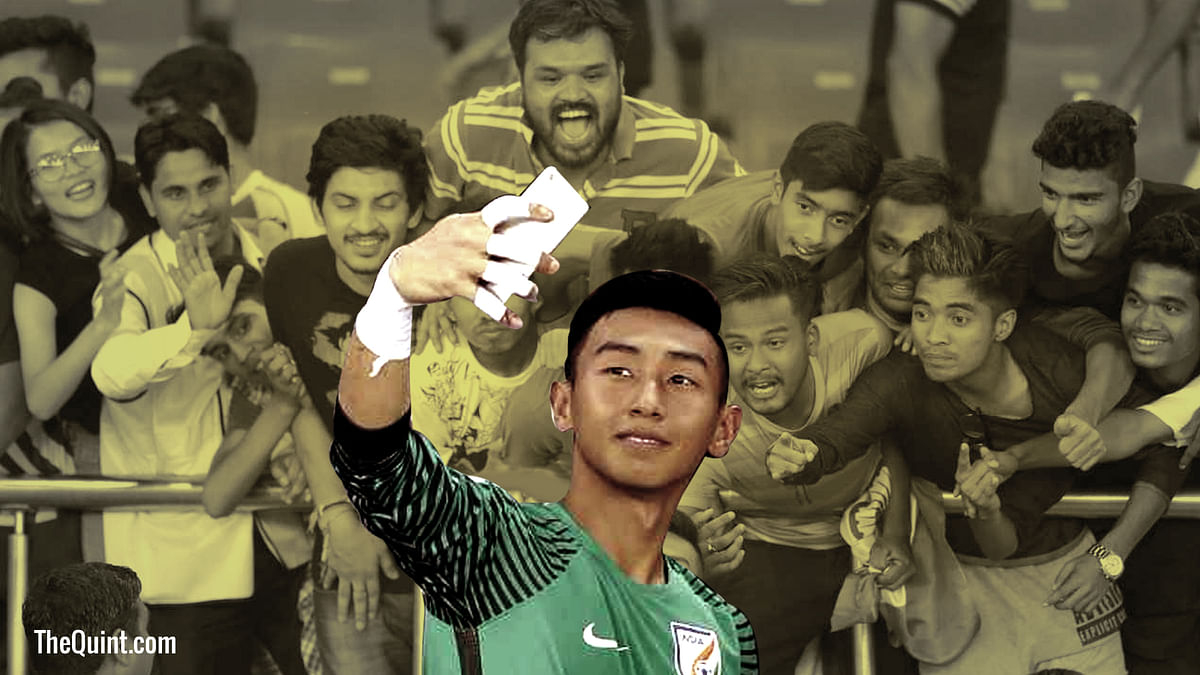 Indian keeper Dheeraj Singh takes a picture with fans after the match against Colombia.