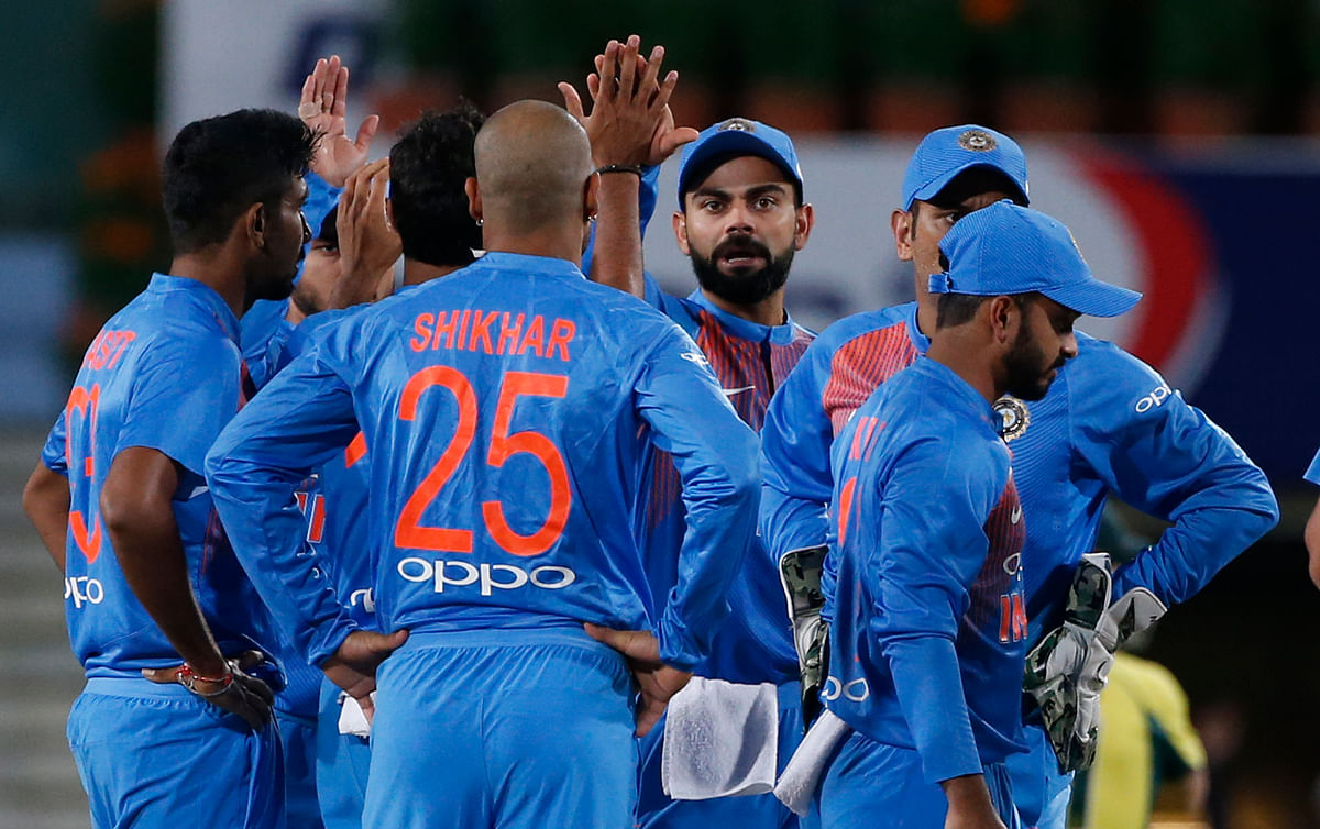 Indian cricketers celebrate the dismissal of Australia's David Warner during their first T20 cricket match in Ranchi
