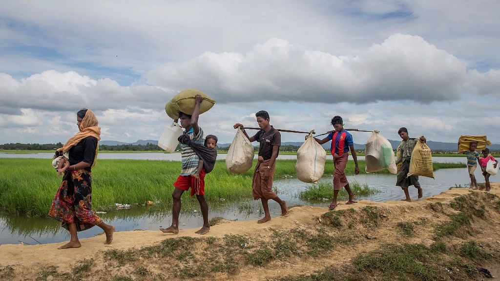 Rohingya Muslims, who spent four days in the open after crossing over from Myanmar into Bangladesh, carry their children and belongings after they were allowed to proceed towards a refugee camp, at Palong Khali, Bangladesh