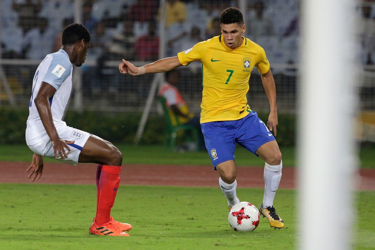 Brazil's Paulinho controls the ball beside England's Lewis Gibson.
