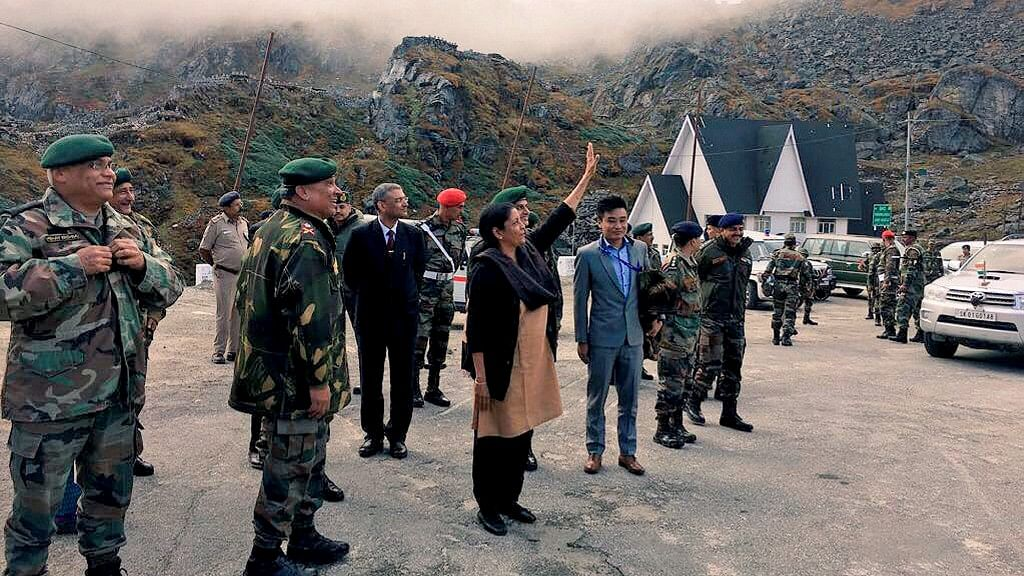 Nirmala Sitharaman waving at Chinese soldiers from across the fence, who were taking pictures on her reaching Nathu La.