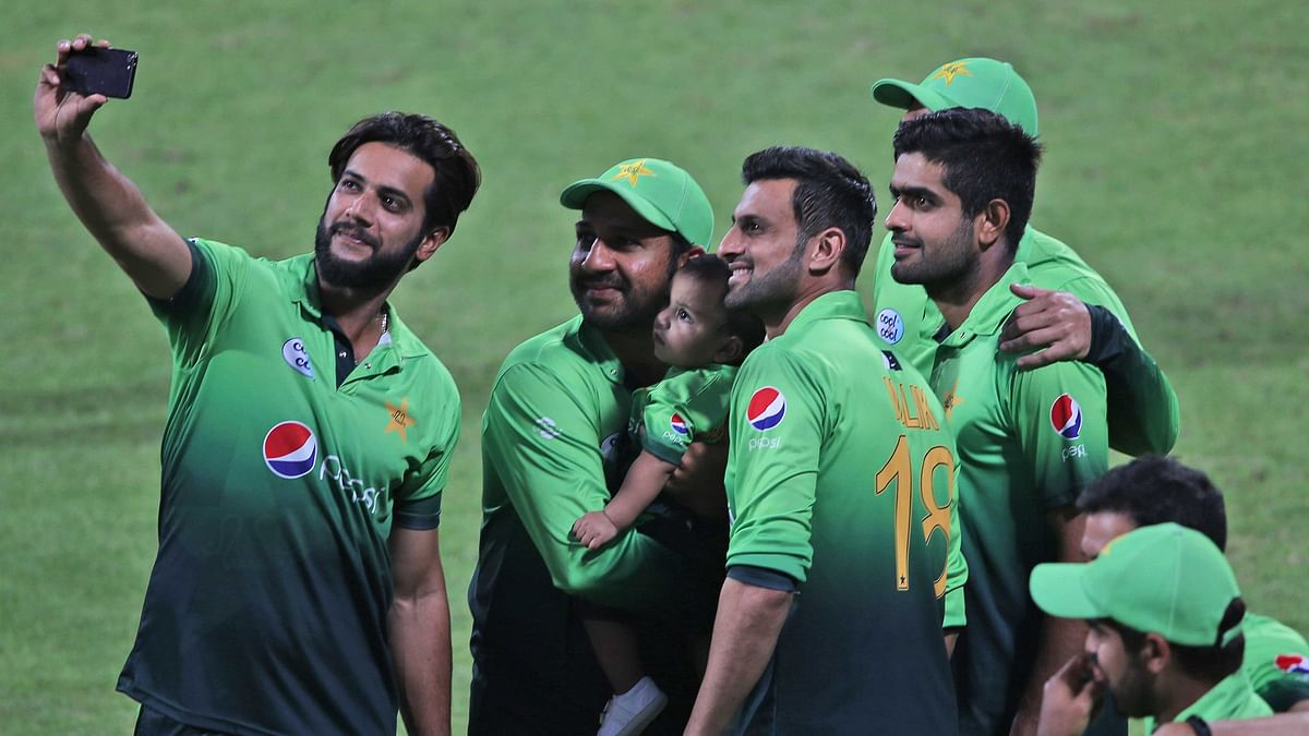 Pakistan's Sarfaraz Ahmed holds his child while taking selfie with his teammates after they beat Sri Lanka in fifth ODI