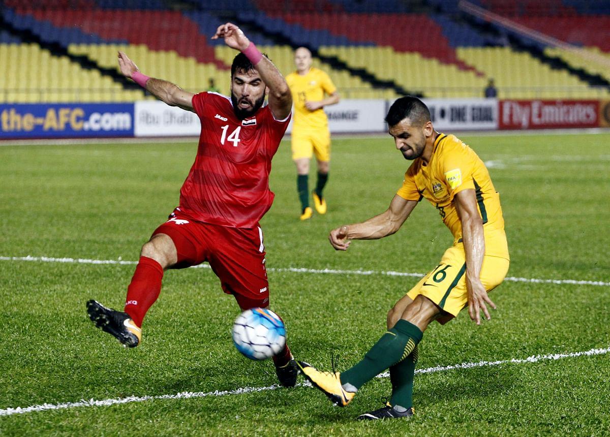 Syria's Tamer Haj Mohamad challenges Australia's Aziz Behich.