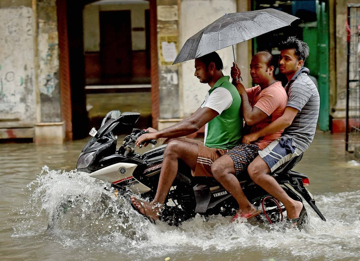 People on a motorcycle wade through a flooded street in Kolkata on Monday. (Photo: PTI)
