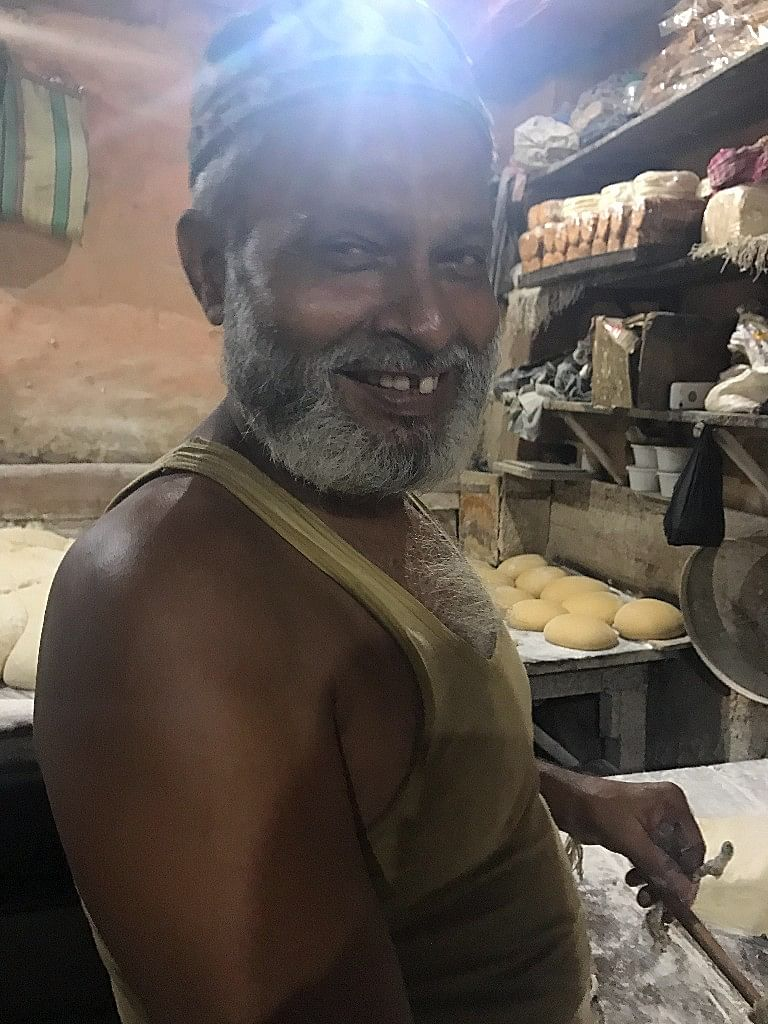A worker at the bakery smiles as he starts his chores.
