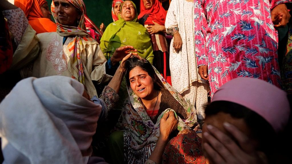 Women console a relative of Yasmeena, a woman who according to local media was killed by unidentified gunmen in Pulwama district, during her funeral in Khonmoh, south of Srinagar.