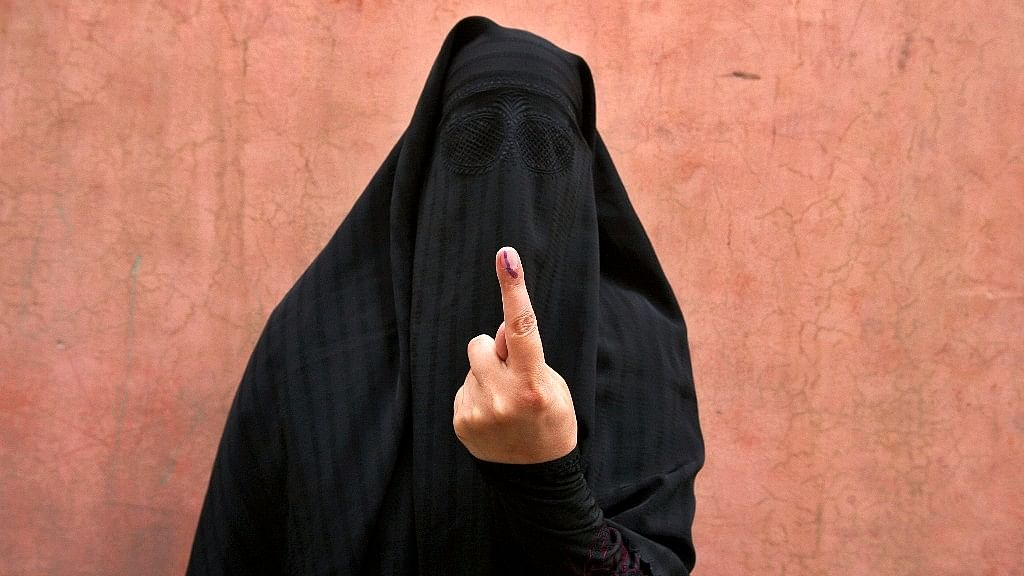 A veiled Muslim woman shows her ink-marked finger after voting outside a polling station in Doda district, north of Jammu.