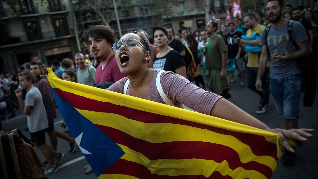 A woman carries an independence Catalan flag as demonstrators march downtown Barcelona, Spain on Tuesday, 3 October 2017.
