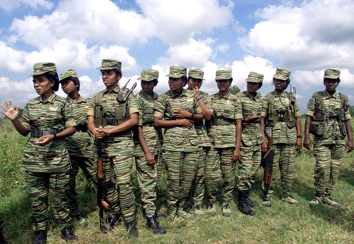 Women fighters of the Liberation Tigers of Tamil Eelam (LTTE) stand on the rebel side of a border crossing in Omanthai in north-central Sri Lanka on 15 February 2002.