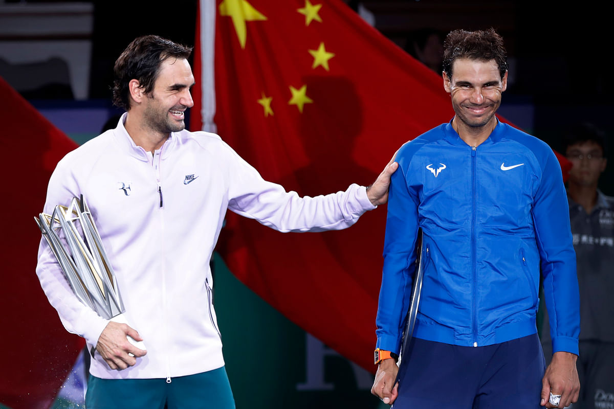 Roger Federer of Switzerland, left, shares a light moment with Rafael Nadal after winning their men's singles final match in the Shanghai Masters tennis tournament at Qizhong Forest Sports City Tennis Center in Shanghai, China, Sunday
