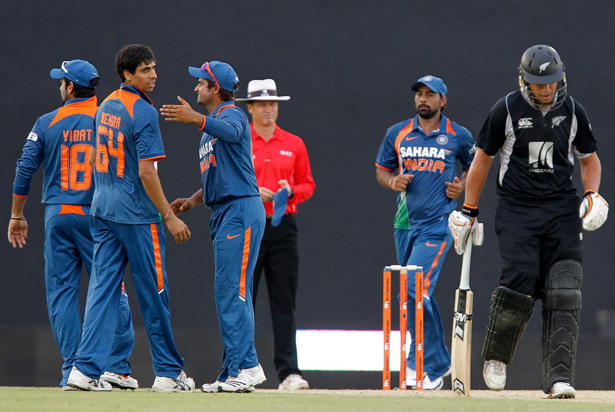 Ashish Nehra celebrates a wicket with his teammates.