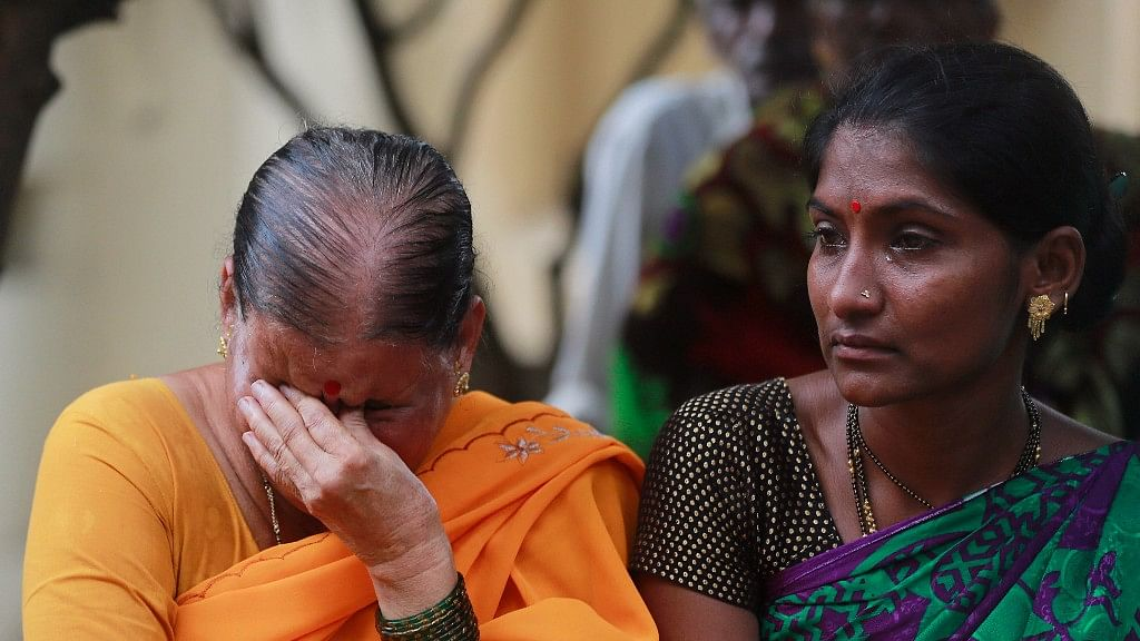 Women mourn outside a morgue for relatives killed in the stampede at Mumbai's Elphinstone Road station.