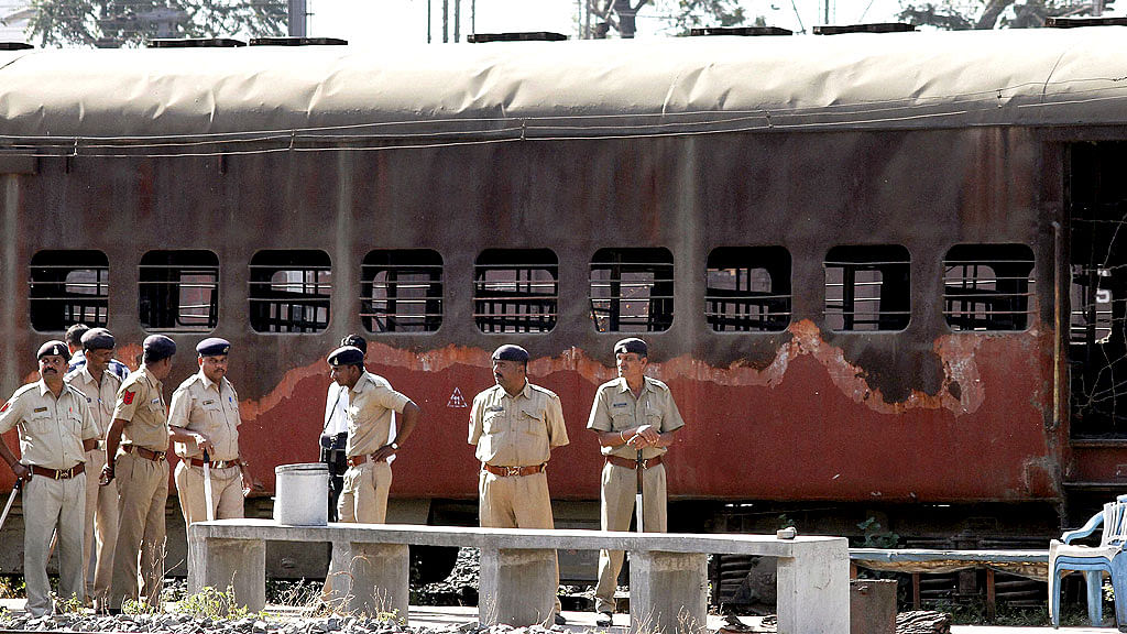 Police guard a train coach that was set ablaze in Godhra in 2002.
