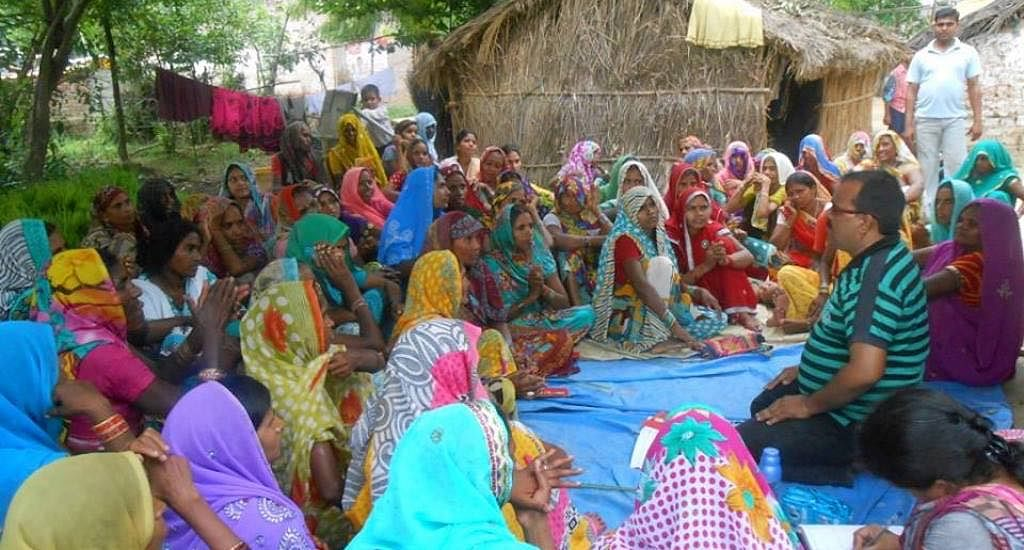 Women of Nari Sangh, the collective, hold discussions with representatives of a community-based organization about the village clinic.