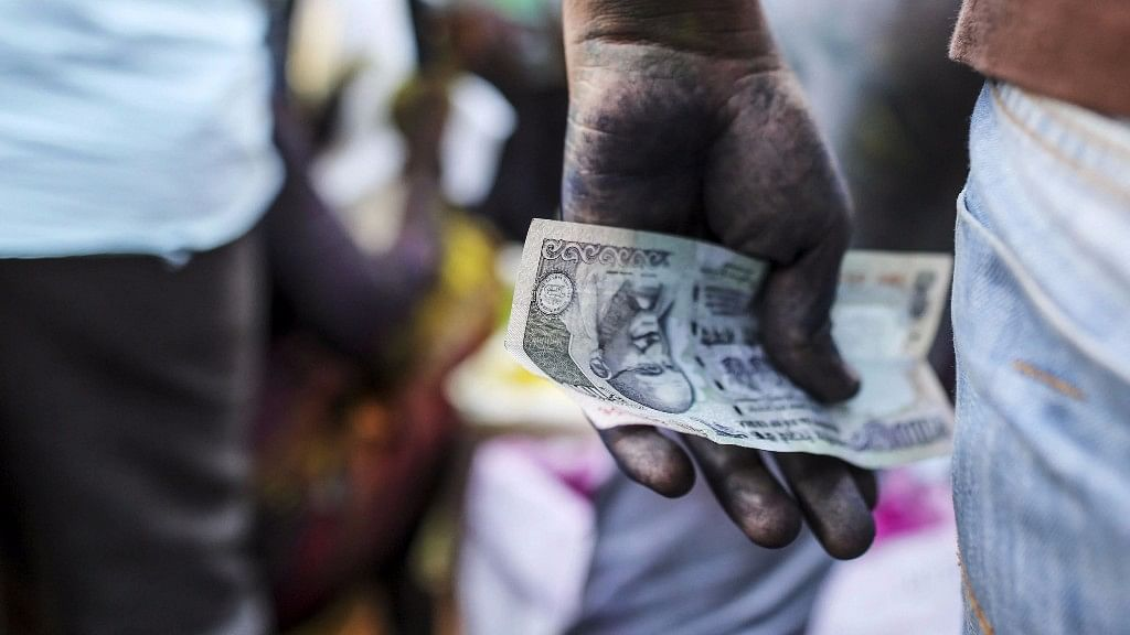 A vendor holds an Indian one hundred rupee banknote at a market stall in Mumbai on 11 March  2017.