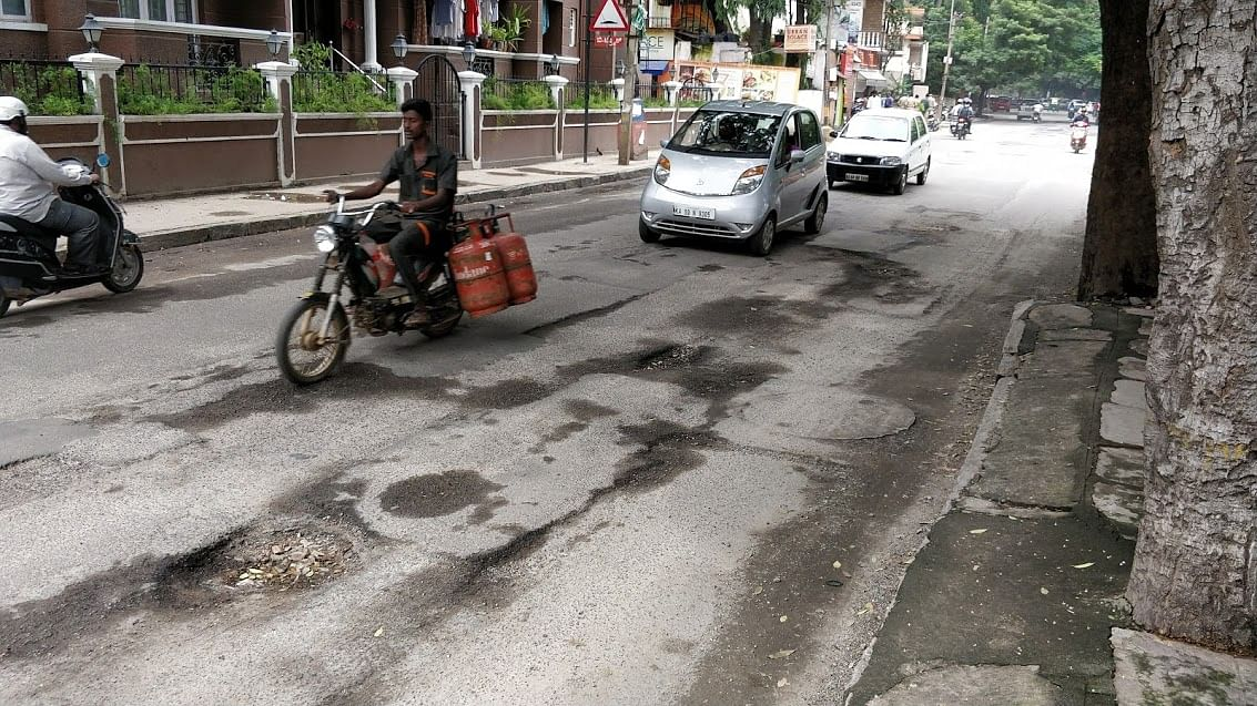 A potholed road in Bengaluru. <i>(Photo: <b>The Quint</b>)</i>
