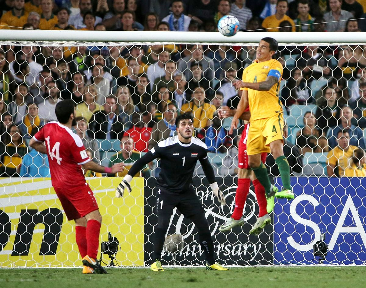 Australia's Tim Cahill, right, scores from a header against Syria.