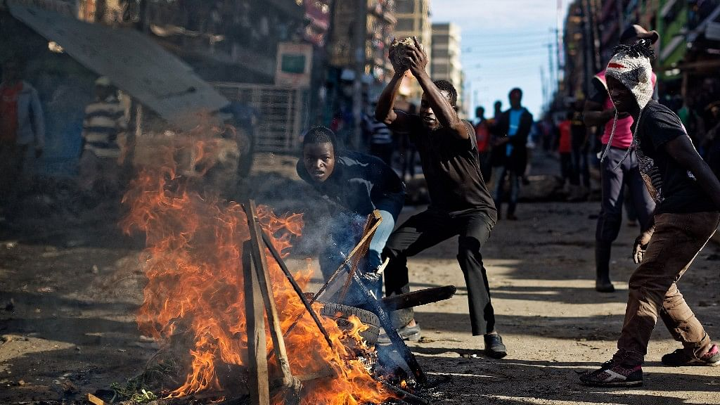 Opposition protesters watch riot police from behind a burning barricade, during clashes with police in the Mathare slum of Nairobi, Kenya on Thursday, 26 October 2017.