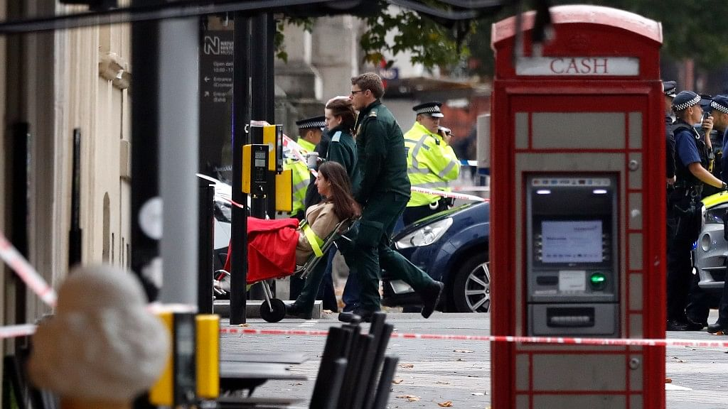 Ambulance personnel push a woman on a stretcher at the scene of an incident in central London on Saturday, 7 October.