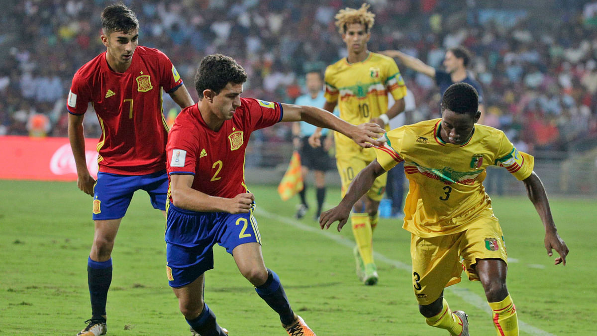 Mali's Djemoussa Traore, right, controls the ball past Spain's Mateu Jaume.