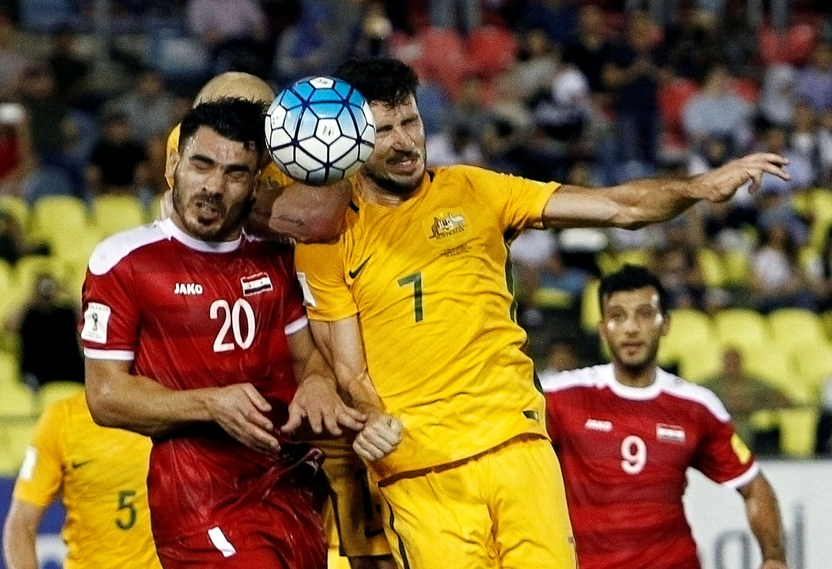 Syria's Khaled Almbayed and Australia's Mathew Leckie fight for the ball.