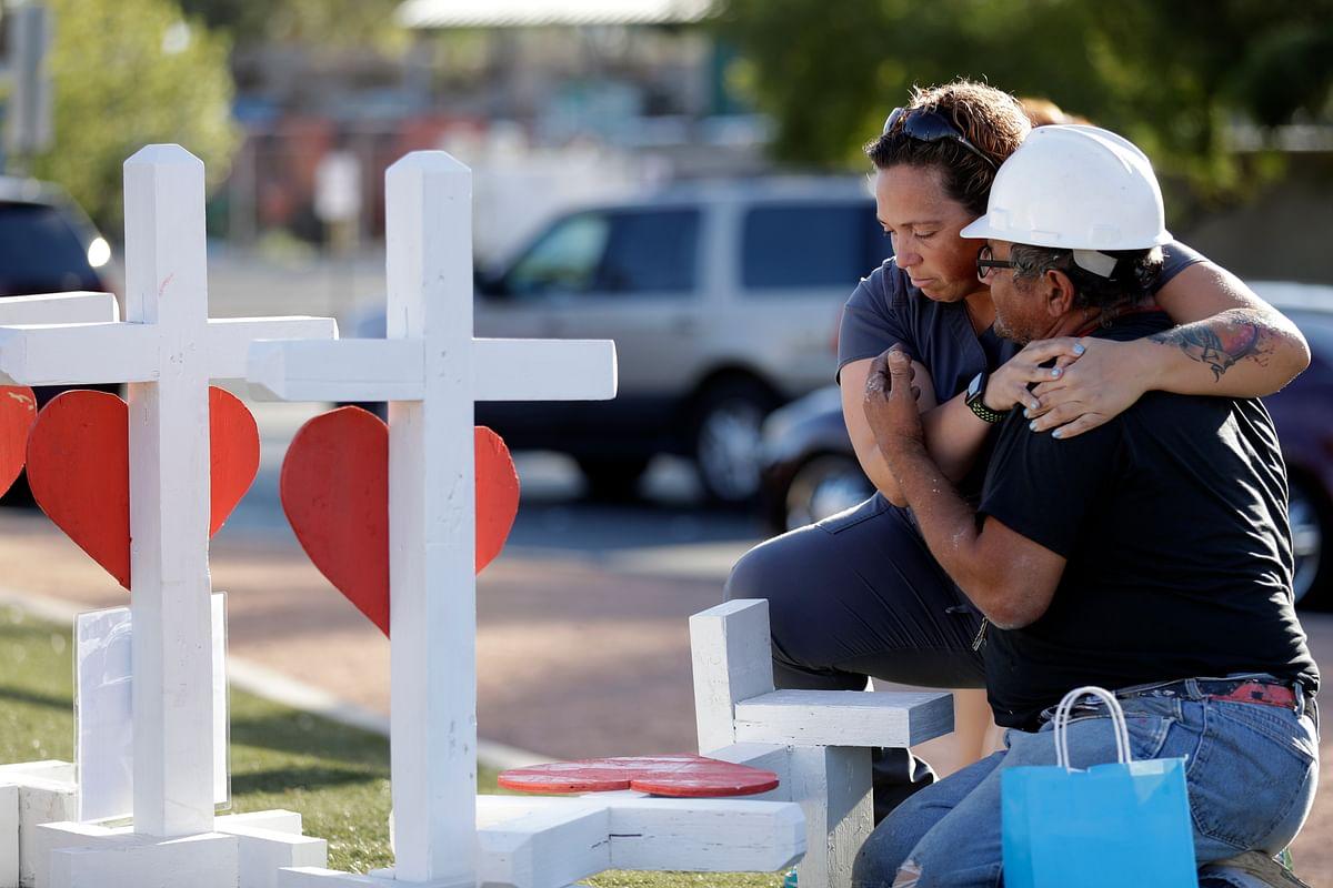 Ebony Saunders, left, hugs Greg Zanis in front of his memorial crosses, on 5 October, in Las Vegas.
