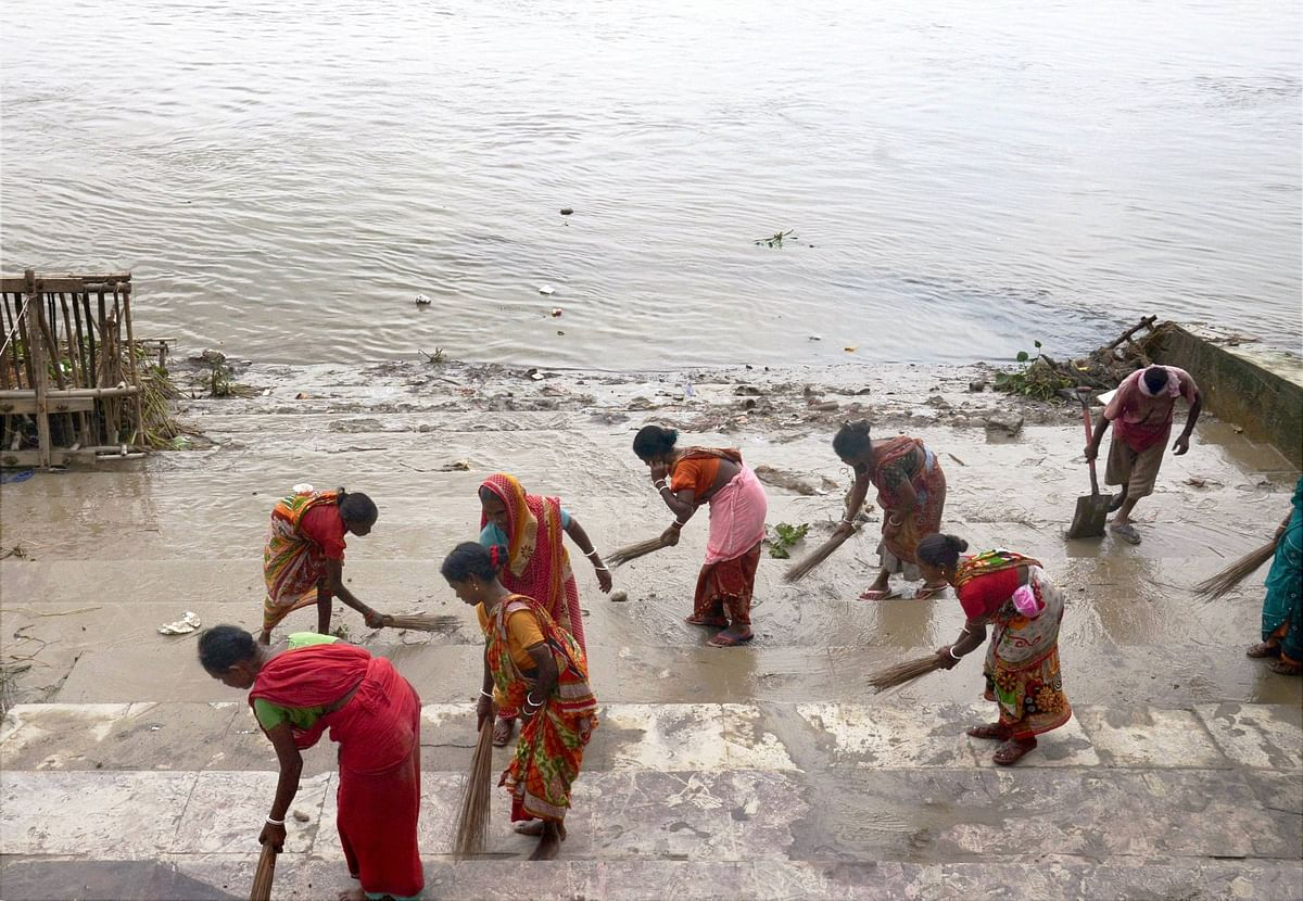 Employees of the Kolkata Municipal Corporation work to clean a ghat by the river Ganga after the completion of immersion of Durga puja idols, in Kolkata on Thursday
