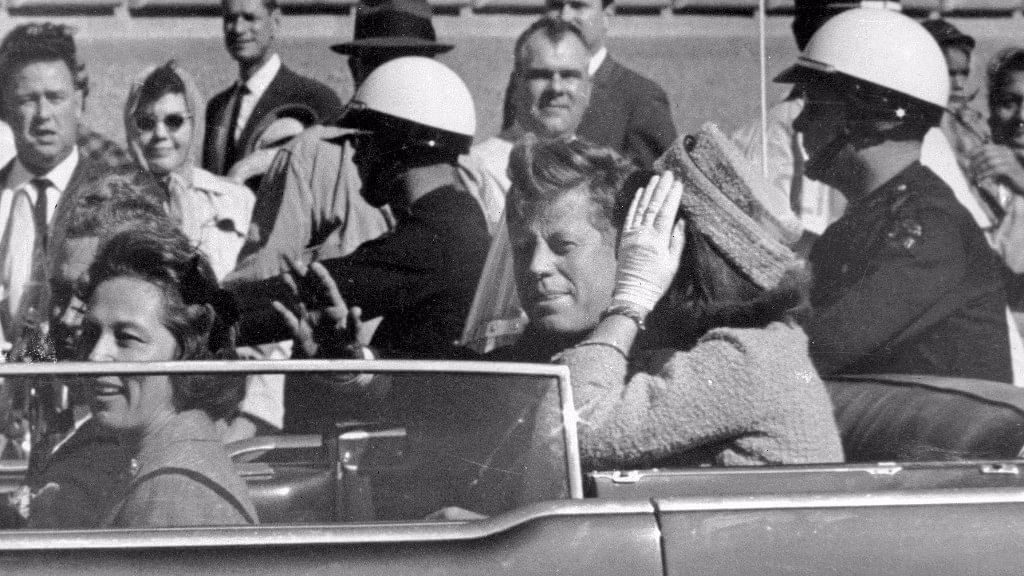 In this 22 November 1963 file photo, President John F Kennedy waves from his car in a motorcade in Dallas, right before his assassination.