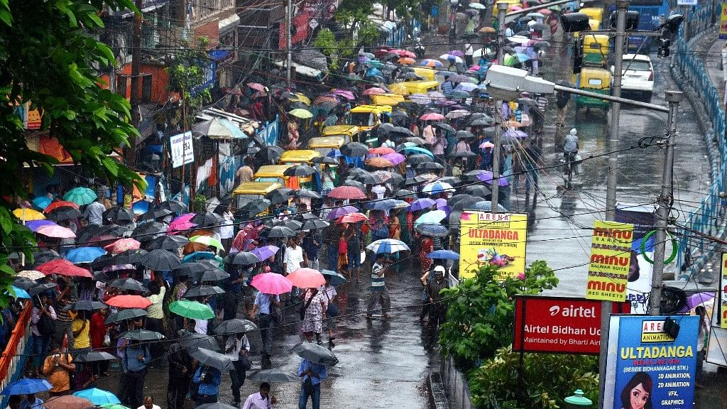 Commuters wait for buses and taxis during heavy rainfall in Kolkata on Monday.