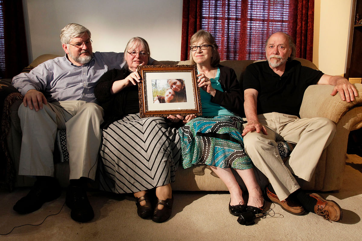 In this 4 June 2014 file photo, from left, Patrick Boyle, Linda Boyle, Lyn Coleman and Jim Coleman hold a photo of their kidnapped children.