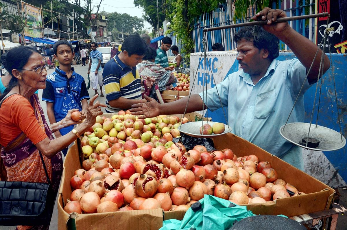 Customers queue up to buy fruits on the occasion of Lakshmi puja festival at a market in Kolkata on Thursday