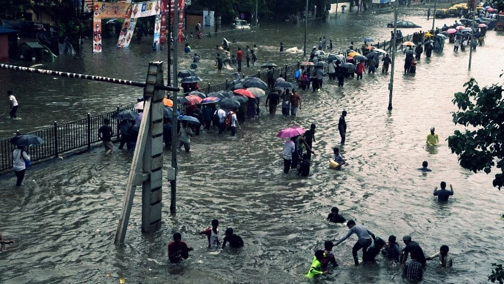 People walk through a waterlogged street following heavy rains in Mumbai. Photo used for representational purpose.
