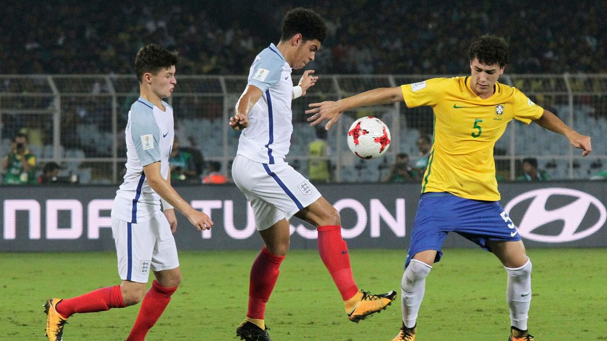 Brazil's Victor Bobsin duels for the ball against England's Morgan Gibbs.