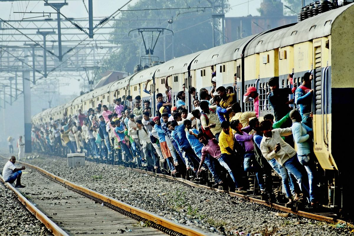 Passengers hang from the coaches of a train traveling to Patna for the Chhath puja. <i>(Photo: PTI) </i>