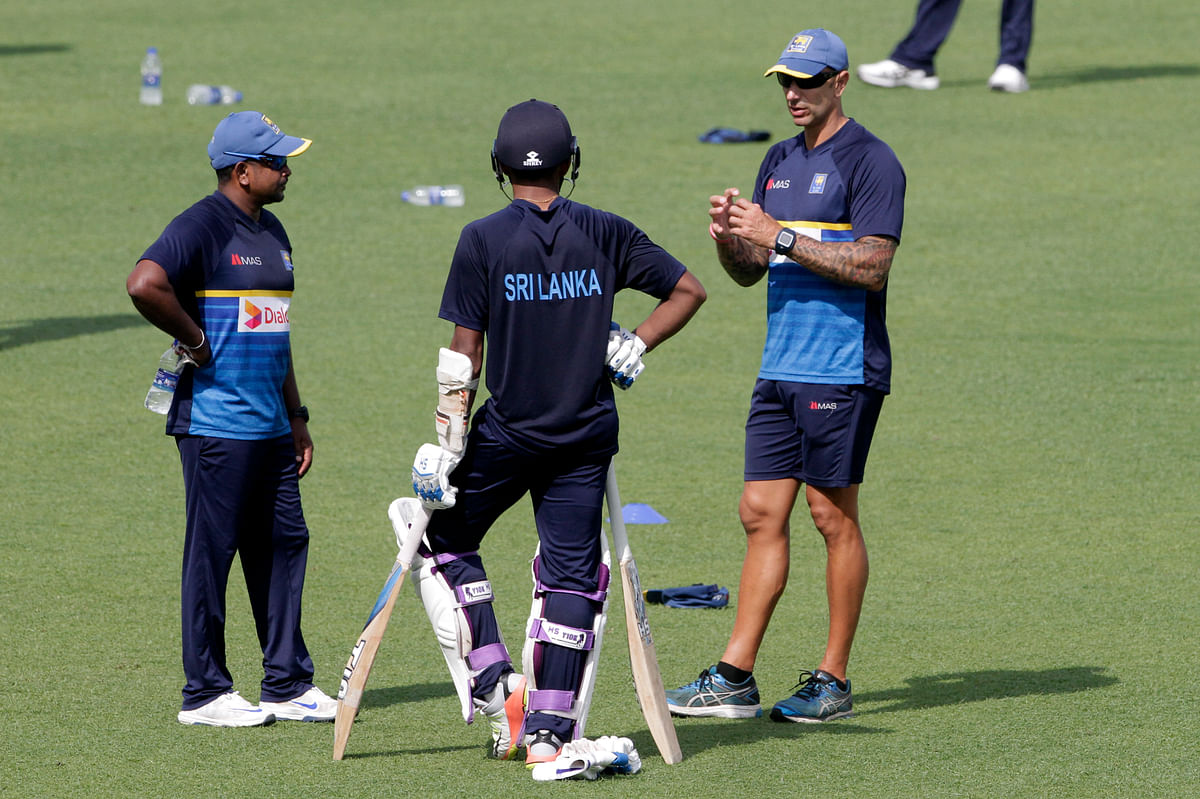 Sri Lanka coach Nic Pothas, R, talks with Rangana Herath, L and another player during practice session prior to their first test match at Eden Gardens in Kolkata, India, Tuesday, Nov. 14, 2017.