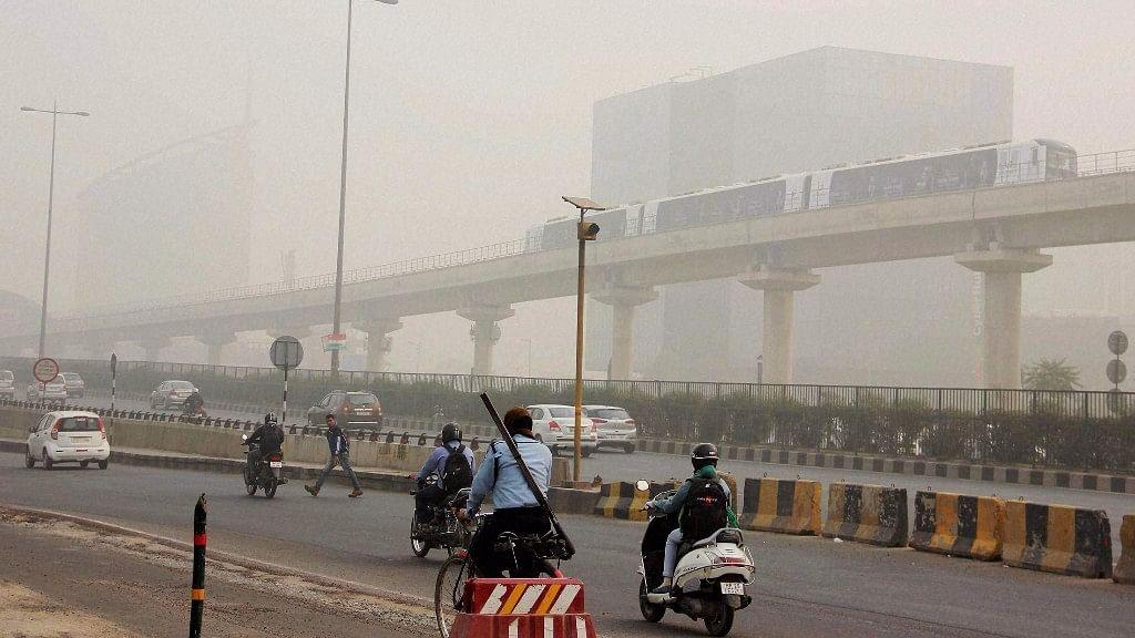 People commute in dense smog in Gurugram on Monday.