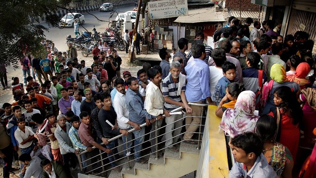 People stand in a queue to deposit and exchange discontinued currency notes outside a bank on the outskirts of New Delhi. Image used for representational purposes.