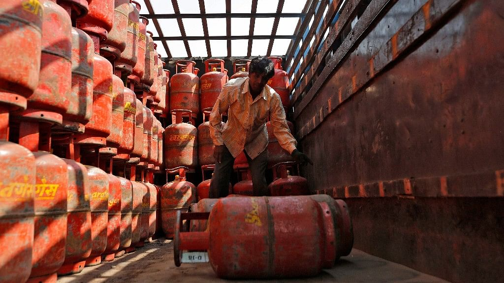 A worker unloads LPG cooking cylinders from a supply truck outside a distribution centre.
