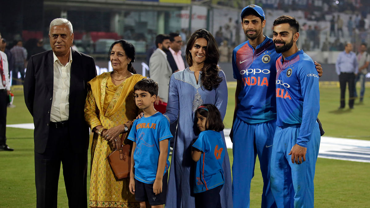 India's Ashish Nehra, second right, pose with his family, to his left and captain Virat Kohli, right, as he bids farewell at the end of his last international match, during their first Twenty20 cricket match against New Zealand in New Delhi