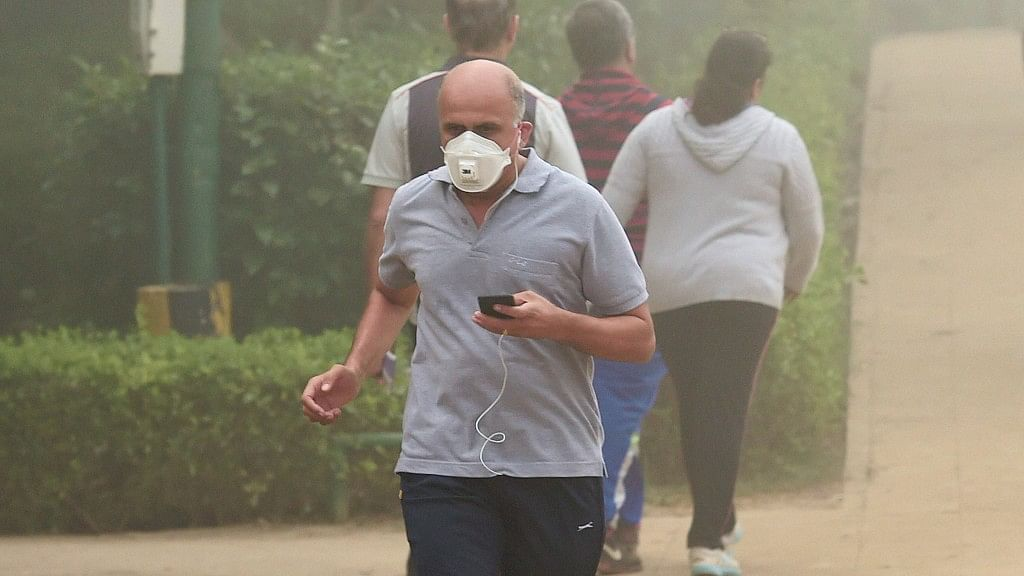 A man, wearing an anti-pollution mask, jogs through smog at Lodhi Garden in New Delhi.