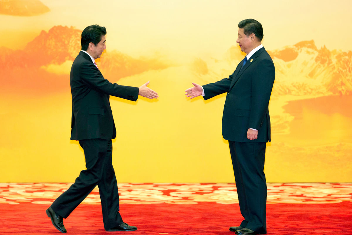 In this 11 November 2014 file photo, Japan's Prime Minister Shinzo Abe reaches out to shake hands with Chinese President Xi Jinping during a regional economic meeting in Yanqi Lake, Beijing.