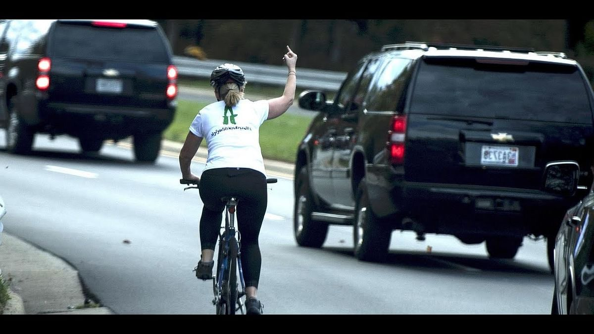 Cycling woman shows Trump he finger as his car drives by her.