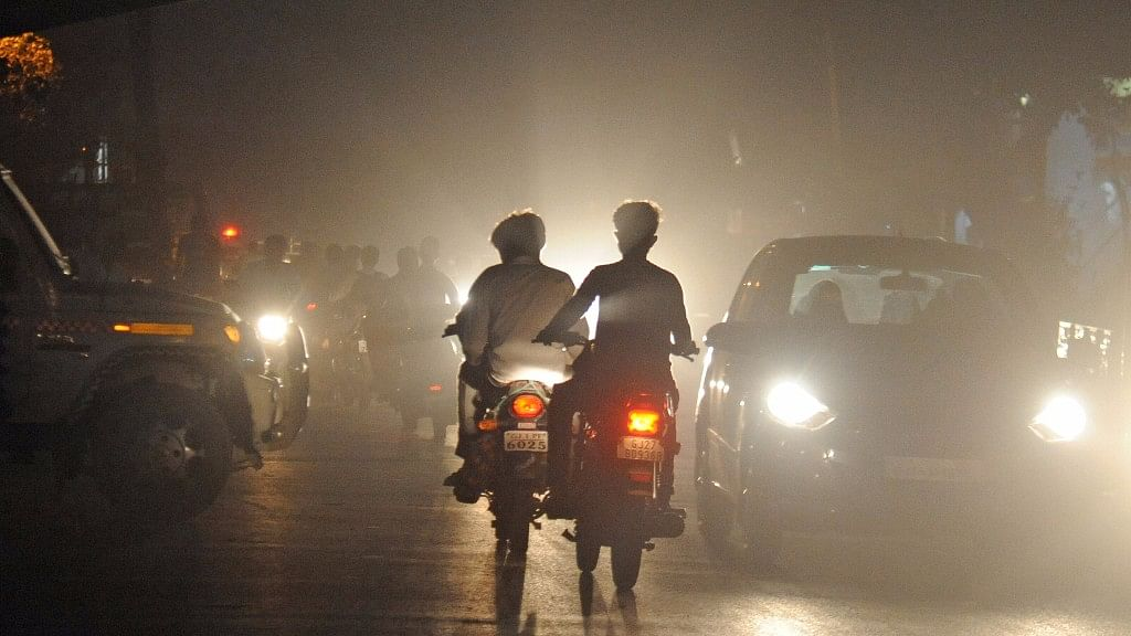 Traffic pushes through a thick layer of smog in Ahmedabad.