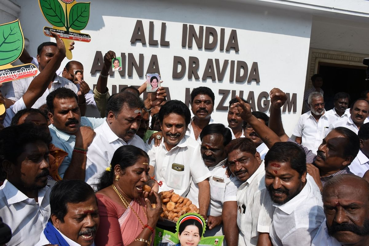 AIADMK workers of the ruling faction celebrate after the Election Commission decided to allot the 'two leaves' election symbol to the party in Chennai.